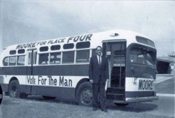 Image of Charles B. Moore (1964), in front of his campaign bus when he ran for the Texas House of Representatives.