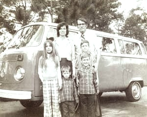 Image of Charles and Judy Moore with the kids in front of their VW bus.